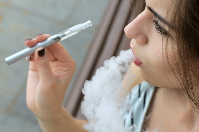 Girl smokes an electronic cigarette